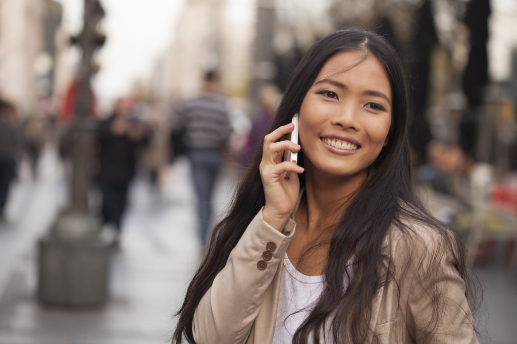 Smiling young woman standing on the street and talking on the phone.