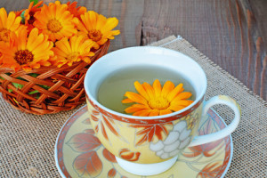 Marigold herbal tea and flower on wooden table.